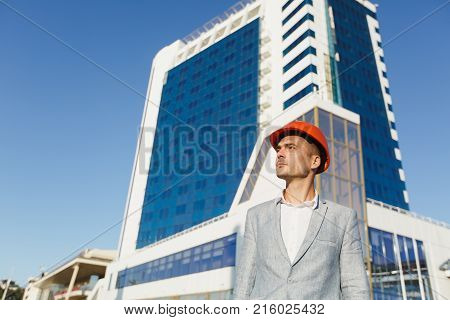 Unshaven Successful Business Man In Gray Suit And Protective Construction Orange Helmet On Building