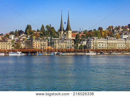 Lucerne, Switzerland - 3 October, 2015: buildings of the city of Lucerne along Lake Lucerne, towers of the Church of St. Leodegar. Lucerne is a city in central Switzerland, it is the capital of the Swiss canton of Lucerne.