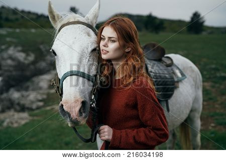 Beautiful young woman on nature in the mountains walking with horse.