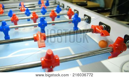 Table football soccer game kicker . Table football game, Soccer table with red and blue players. Young friends playing table football together indoors.