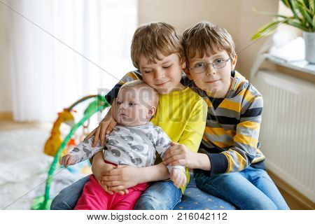 Two little happy kid boys with newborn baby girl, cute sister. Siblings. Brother holding baby girl on arm. Kids bonding. Family of two bonding, love.