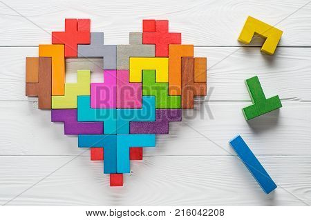 Heart made of colorful wooden shapes top view flat lay. Health background concept. Logical tasks. Conundrum find the missing piece of the proposed.