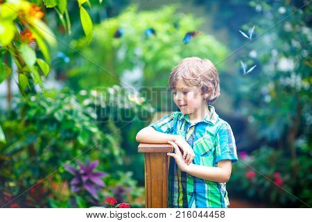 Little blond preschool kid boy discovering flowers, plants and butterflies at botanic garden. Schoolchild interested in biology. Active educational leisure with preschool kids in museum.