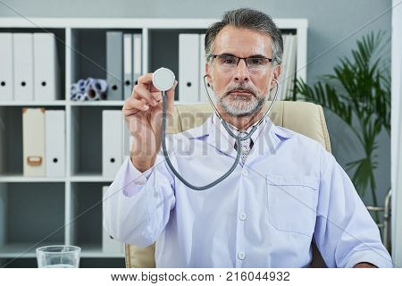 Unsmiling mature doctor with stethoscope in hand