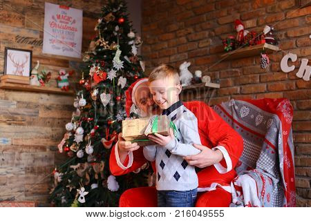 Happy male child runs up to Santa Claus and sits on knees. kid embraces Christmas grandfather whispers in ear cherished desire. handsome young European-looking boy dressed warm sweater blue jeans with socks, gray long beard red suit white trim pointed cap