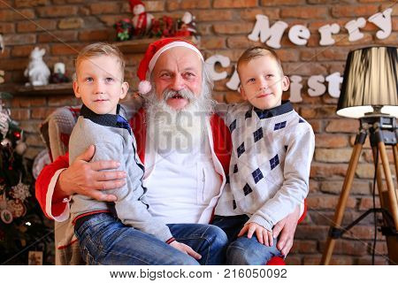 Lovely boys of same appearance sit on lap Santa Claus who sits large and soft armchair whisper in ear cherished wishes for New Year cozy spacious room decorated Years holidays with floor lamp, walls which hang Christmas posters, And high bright tree, unde