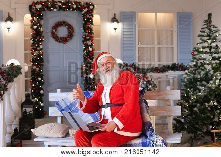 Cheerful Santa Claus making video call in cozy apartments. Gladden man in red costume satisfying with joyful ambience. Concept of communication with Father Christmas using modern gadget. poster