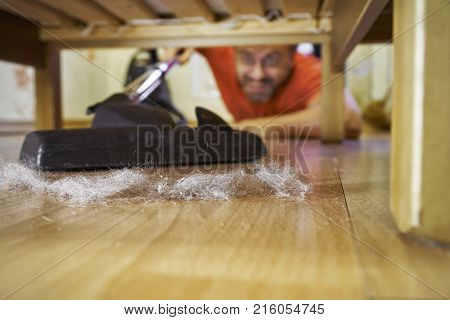Man hoovering a floor under a bed lying on the floor