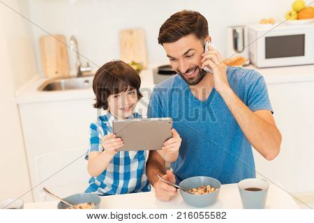 Father and son have breakfast in the light kitchen. They are in their house together. They communicate on the tablet with boy's mom. They are in a good mood. They have a happy family.