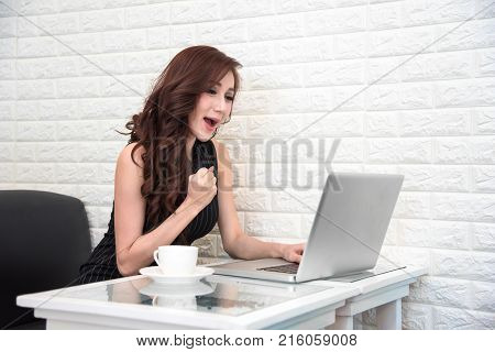 Asian Woman Happy After Success New Start Up Project Or Online Bidding With Laptop. Business And Suc