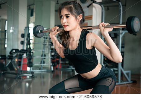 Sports Woman Lifting Weight In Fitness Gym. Workout Exercise And Body Build Up Concept. Barbell Lift