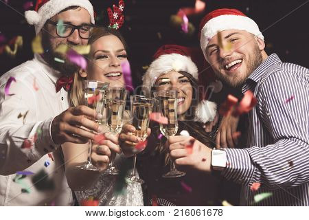 Four young people on a New Year's eve party making a toast at midnight