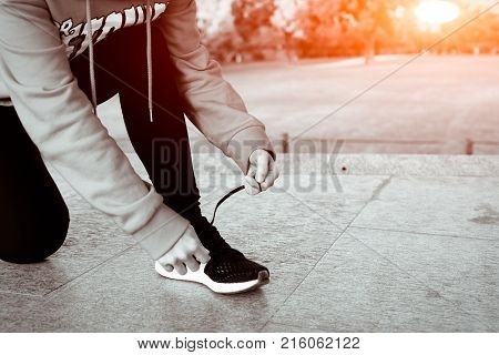 close up young woman tying shoelace while walking sunny day in winter season- B&W filter