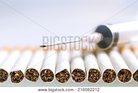 Cigarette and syringe on a white table. Smoking causes cancer and emphysema. Health Care concept.