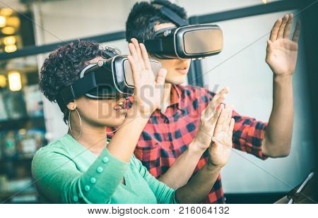 Multiracial couple in love going beyond racial diversity through virtual reality glasses - Young people having fun using new technology - Friends testing vr goggles connection with futuristic visions