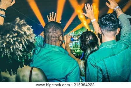 Young people dancing at night club - Hands up on laser show lights at nightclub after party - Nightlife concept with afterparty crowd celebrating dj concert festival event - Teal and orange filter