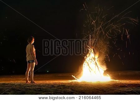 Young woman traveler feeling heat of beach bonfire with sparks in the night - Wanderlust travel concept with adventure girl tourist wanderer on excursion in Thailand island - Dark natural lighting