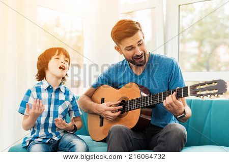 The father teaches his son to play the guitar. He helps him pick up guitar chords. They are in a good mood. They sing the song together.