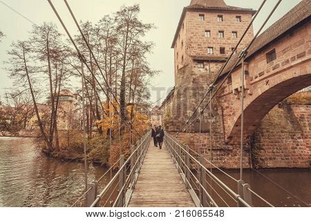 People walk along a wooden suspension bridge across the river in the historic city of Nuremberg with historical walls. Old Bavaria of Germany.