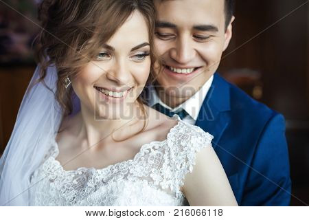 close up portrait of young groom and beautiful bride hugging and smiling. Bride in beautiful wedding white dress and asian groom in dark blue suit. Concept of happy newlywed couple