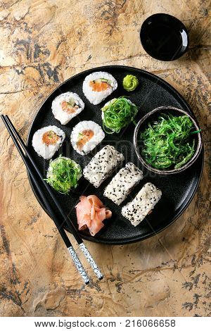 Homemade sushi rolls set with salmon, sesame seeds serving in black plate with pink pickled ginger, soy sauce, wasabi, seaweed salad, chopsticks over brown stone background. Top view, space