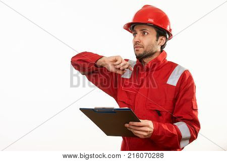 Worker in red safety workwear uniform and helmet holding clipboard, working and showing something isolated on white background with copy space. Close-up portrait