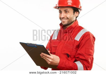 Young male builder or manual worker in red hard hat with clipboard taking notes isolated on white background with copy Space.construction, building and people concept