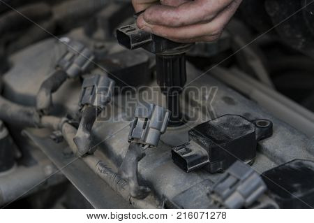 Replacement of spark plugs in the car. The specialist's hand pulls the spark plug out of the socket. Repair of the old machine. Hands of the old elderly master.
