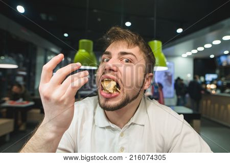 A funny man with a mouth full of food looks at the camera. The hungry man got a full mouth of fast food.