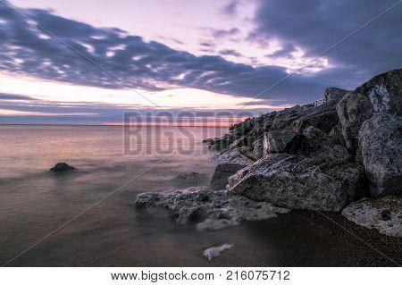 Michigan Great Lake Rocky Coastline Beach Sunrise. Sunrise on a rocky Lake Huron beach in Lexington, Michigan.
