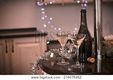 Still life with two glasses of champagne with a bottle and a cork on a black table in a kitchen. Warm colors. Sepia background.