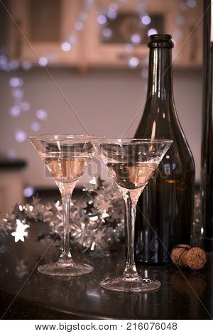 Still life with two glasses of champagne with a bottle and a cork on a black table in a kitchen. A silver shiny garland on the table. Warm sepia colors. Blurred kitchen furniture at the background