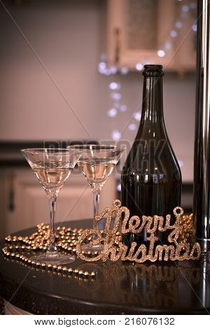 Still life with two glasses of champagne with a bottle and a cork on a black table in a kitchen. A chain of gold beads and a gold Merry Christmas inscription. Warm sepia colors. Blurred kitchen furniture at the background