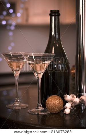 Still life with two glasses of champagne with a bottle and gold shiny ball on a black table in a kitchen. Warm sepia colors. Blurred kitchen furniture at the background