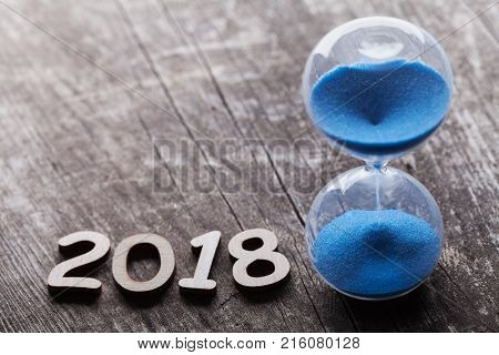 New year 2018 time concept. Hourglass or sandglass on rustic wooden table.