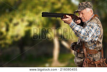 Man senior gun senior citizen grey hair green background
