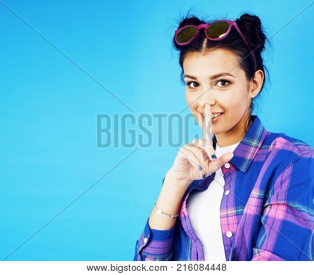 young pretty woman fooling around on blue background close up smiling, lifestyle people concept copyspace