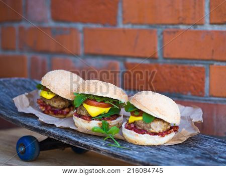 Burgers on the sckateboard on brick background. Huge double burger on a wooden board on a wooden background. Really huge burger with another burger close