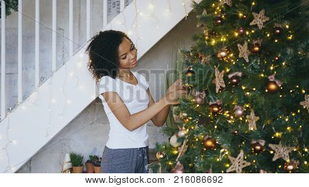 Curly mixed race girl decorating Christmas tree at home preparing for Xmas celebration with her family