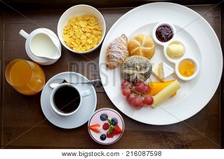 Rich continental breakfast. French crusty croissants, muesli, lots of sweet fruits and berries, hot coffee for morning meals. Delicious start of the day.
