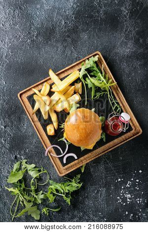 Homemade traditional hamburger with beef, tomato, cheese, aragula, served on wooden slate serving board with french fries and ketchup sauce on dark texture background. Top view with space