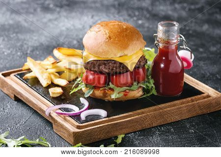 Homemade traditional hamburger with beef, tomato, cheese, aragula, served on wooden slate serving board with french fries and ketchup sauce on dark texture background. Close up