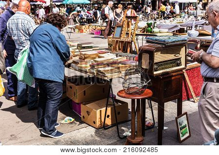 Paris France - Jule 09 2017: People choosing rare and used books vintage goods at the historic flea Aligre Market (Marche d'Aligre) in the Bastille district.
