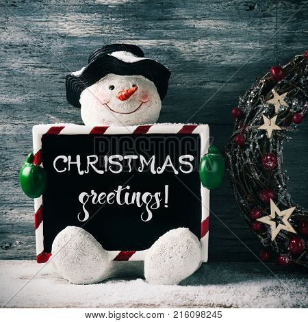 a funny snowman holding a black signboard, with the text christmas greetings written in it, and a christmas wreath against a gray rustic wooden background