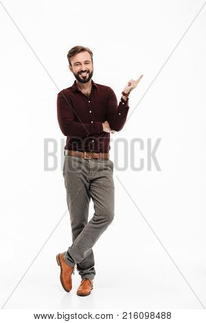 Full length portrait of a confident happy man standing and pointing finger away isolated over white background