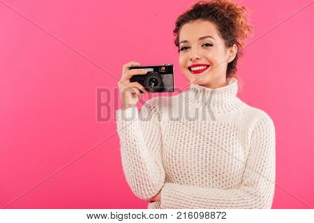 Portrait of a happy young girl holding photo camera and looking at camera isolated over pink background