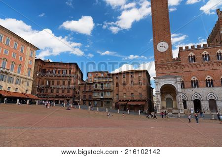 SIENA, ITALY - MAY 25, 2017: Campo Square (Piazza del Campo), Palazzo Pubblico and Mangia Tower (Torre del Mangia). The historic centre of Siena has been declared by UNESCO a World Heritage Site.