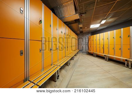 Locker room with rows of orange lockers at fitness center.