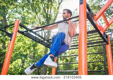 Low-angle view of a strong and determined young man doing amazing pull-up variation during extreme outdoor workout in the applauses of his friends