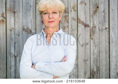 Portrait of a confident senior woman looking at camera while wearing a spotless shirt against a rustic wooden fence